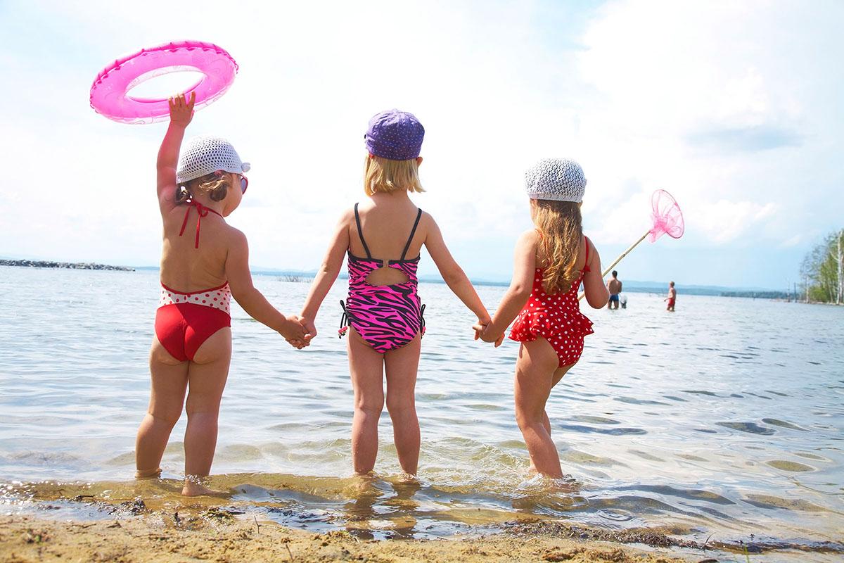 3 kinderen in badpak met voetjes in het water van het veerse meer