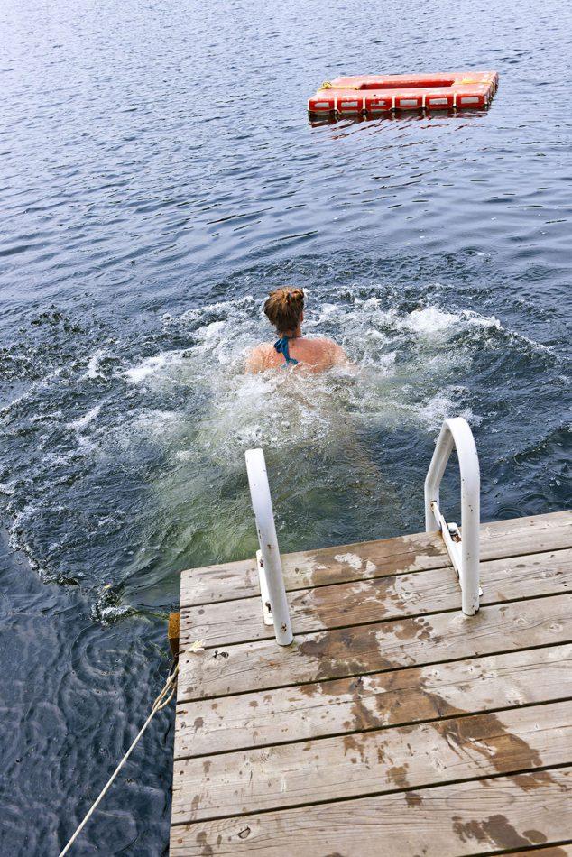 Vrouw zwemt vanaf een steiger in het veerse meer
