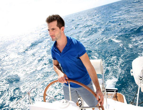Man achter het roer op zeilboot op open zee