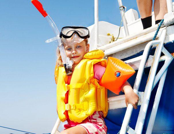 Kindje met duikbril en snorkel die achter de zeilboot gaat zwemmen
