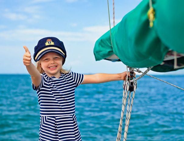 Meisje die haar duim opsteekt op een zeilboot