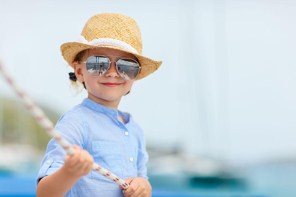 Meisje met hoed en zonnebril houdt landvast vast