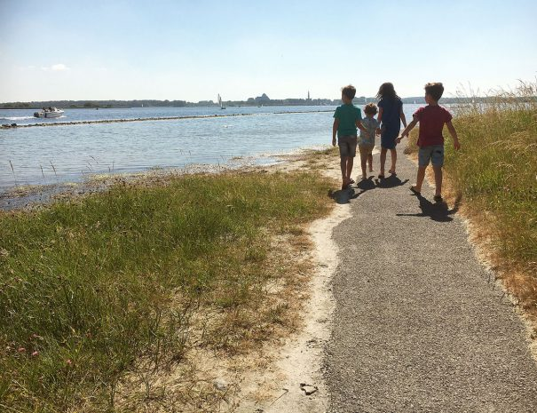 Kinderen wandelen op zonnige dag langs het veerse meer