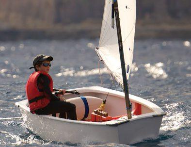 Een huur optimist zeilboot bestuurd door een jongetje met rood zwemvest, zeilend op het Veerse Meer