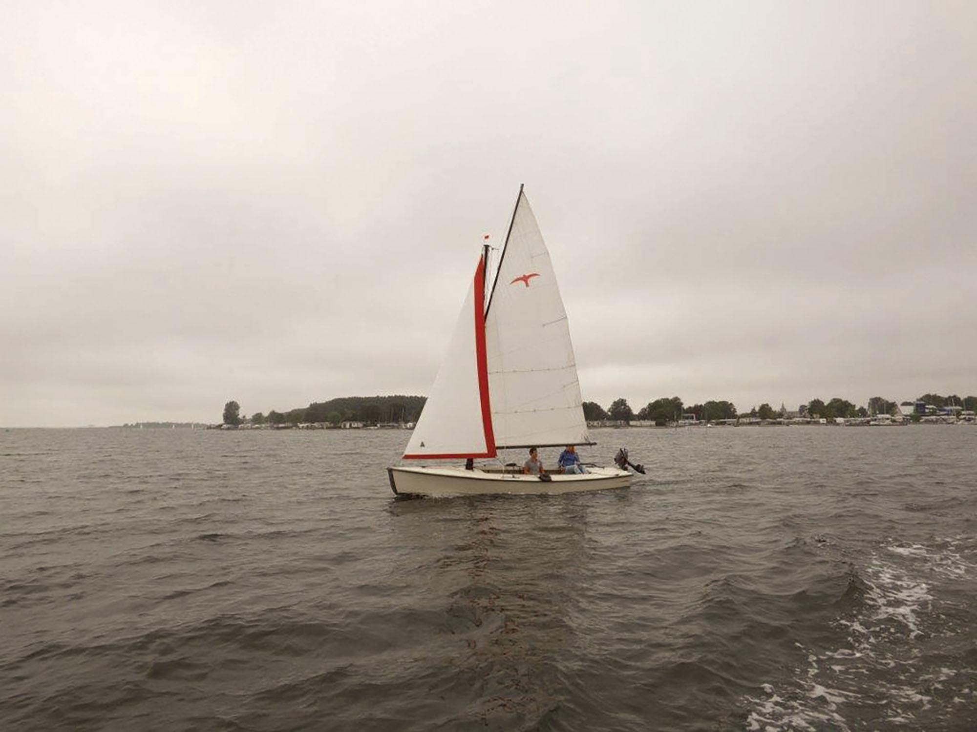 Een witte Valk huur zeilboot met 2 personen zeilend op het Veerse Meer bij Kortgene