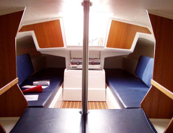 Het interieur van een Fox 22 huur zeilboot, genomen vanaf het 2 persoons bed. Je ziey de opbergruimte, zitbanken/bedden en de kookgelegeheid