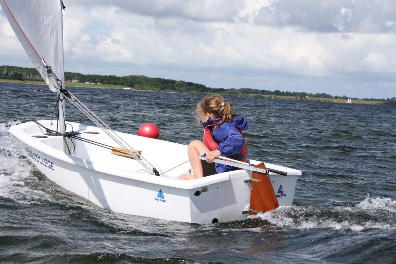 Meisje kwam optimist huren en is aan het zeilen in zeilboot in Zeeland